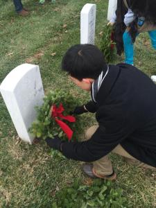 The author lays a wreath on a headstone.